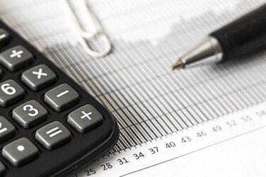 Mustavalkoinen kuva, jossa näkyy taskulaskin, klemmari ja kynä paperin päällä. Paperissa on taulukko.