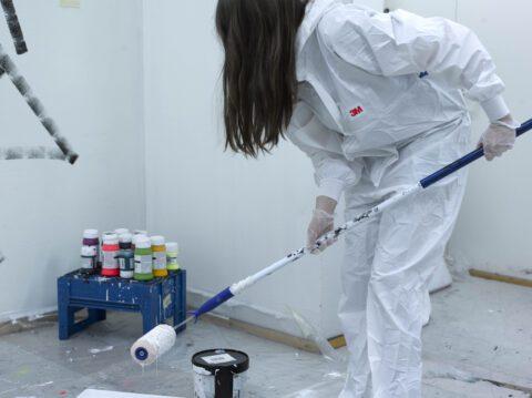 Taiteilija Hannaleena Heiska maalaamassa valkoisessa tilassa