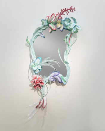 taiteilija, muotoilija Teemu Salosen teos, jossa keskellä epäsymmetrinen peili, jota ympäröivät kukat ja kasvillisuus.