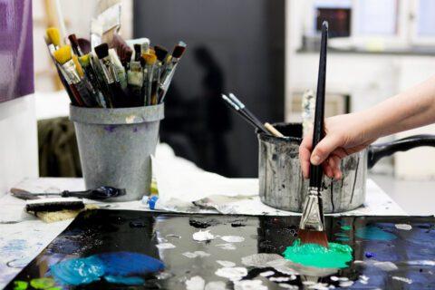 kuva taiteilijan työhuoneesta, jossa taiteilija maalaa teosta. Kuvassa näkyy pensseliä pitävä käsi ja pensseleitä taustalla purkissa.