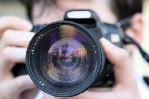 Lähikuva henkilöstä, joka pitelee kameraa kasvojensa edessä. Kameran objektiivi on suunnattu katsojaan ja kamera peittää kuvaajan kasvot.
