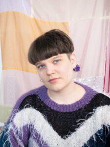 Henkilökuva taiteilija Anni Hauniasta, taustalla vaaleasävyinen, tilkkimäinen kangas.